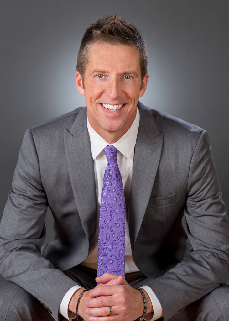 Photo of a white man in a business suit with a purple tie sitting down and smiling