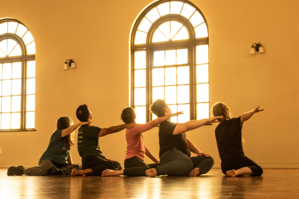 A group of dancers sit in a light filled room with their backs to the camera.